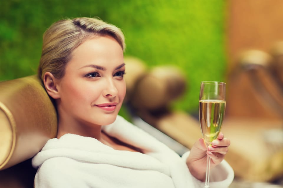 client laying on a treatment chair in bathrobe with a glass of champagne