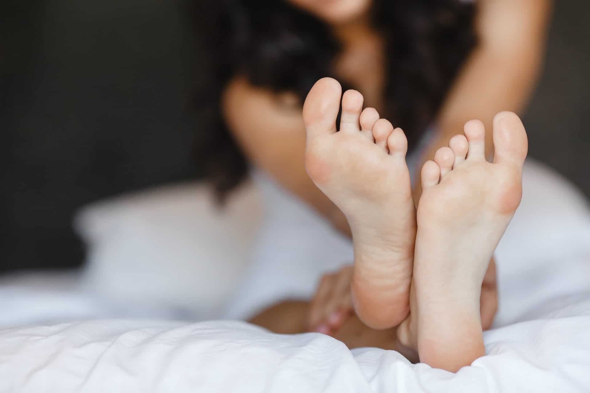 pedicured feet laying on a bed